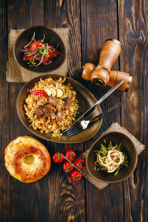 Traditional plov with lamb meat, garlic, onion and salads on the sides