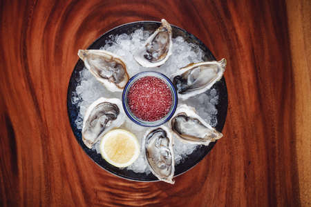 Fresh oysters served on the plate with ice and lemon