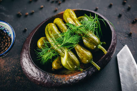 Homemade pickled cucumbers served in the dark bowl and decorated with dill
