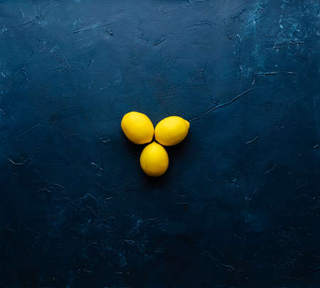 Deep dark blue painted surface that has light blue scuffs. Three lemons placed in the centre