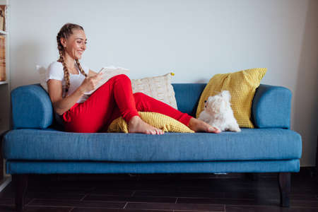 Side view composition of smiling young woman sitting on the couch with her dog and reading book while enjoying weekend at home
