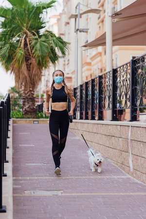 Sporty woman wears a face mask running together with her dog within city streets. Stok Fotoğraf