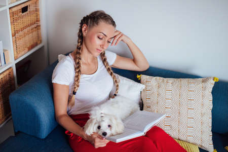 Side view portrait of smiling young woman sitting on the couch with her dog and reading book while enjoying weekend at home Stok Fotoğraf
