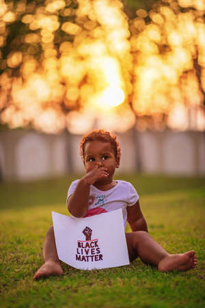 Little African-American baby girl sits on the green grass and holds the poster Black Lives Matter Stok Fotoğraf
