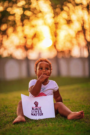 Little African-American baby girl sits on the green grass and holds the poster Black Lives Matter Imagens
