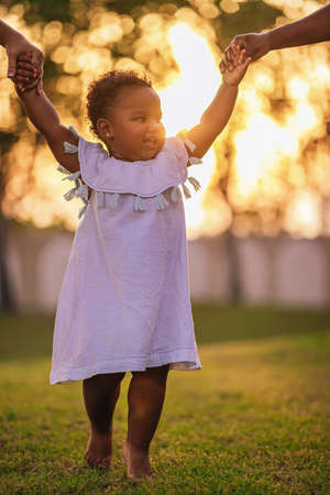 Positive little one and half year African-American girl walks around the lawn and takes her steps holding hands of her parents