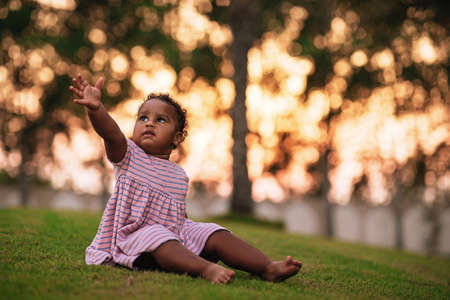 Sweet little African American girl wearing cute pink dress and sits on the grass outdoor with her hand up