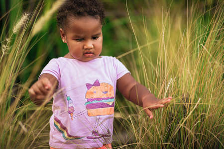Portrait of sweet little African American girl wearing cute colourful outfit and walks on the grass outdoor