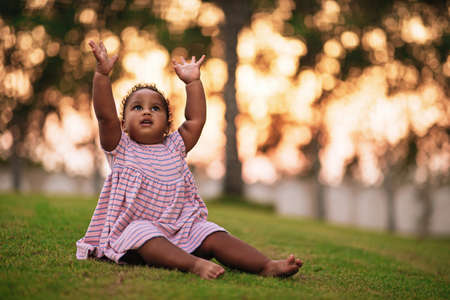 Sweet little African American girl wearing cute pink dress and sits on the grass outdoor with her hands up Stok Fotoğraf