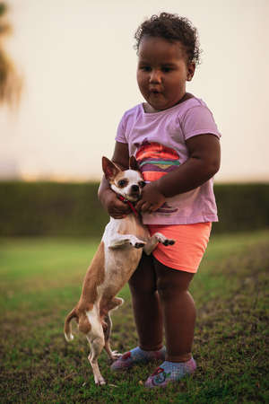 Cute little african american kid holds and hugs her dog in a funny way, both standing on the grass