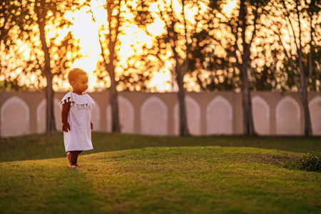 Sweet little African American girl wearing cute pink dress and walks on the grass outdoor