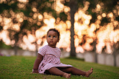 Sweet little African American girl wearing cute pink dress and sits on the grass outdoor