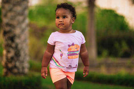Sweet little African American girl wearing cute colourful outfit and walks on the grass outdoor Stok Fotoğraf