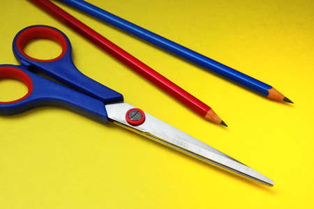 Scissors and pencils on a yellow background a cardboard photo