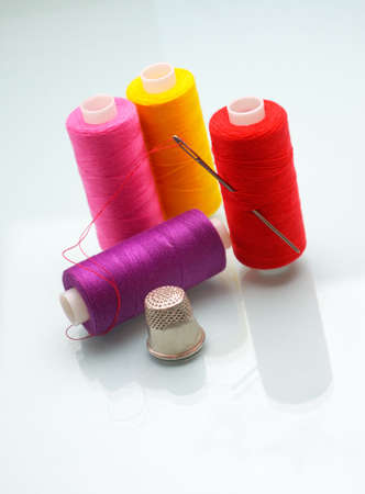 sewing thread coils, thimble and a needle  photo