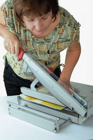 The woman the worker at office cutting a paper with application of a guillotine