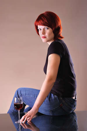 girl c a red wine glass on a dark grey background photo