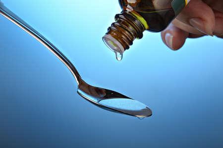 Drop of a medicine bottle On a dark blue background photo
