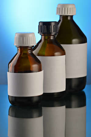 Medicinal mixture in glass small bottles on a gradient  blue background Stock Photo - 10181796
