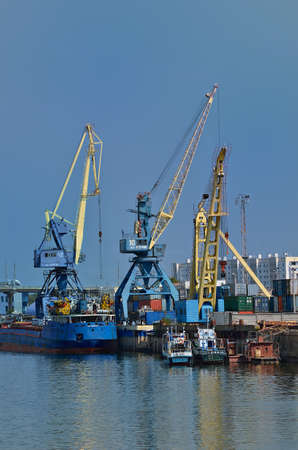 Cranes, barges and boat at a cargo mooring photo