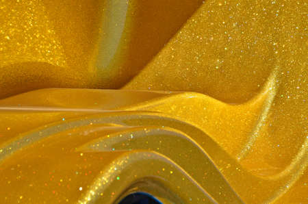 Abstract background of smoothly bent surface with a golden covering photo