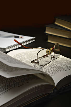 reading glasses: open book and glasses located on a dark table and a dark background