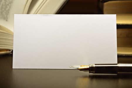 papeleria: Tarjetas de visita y pluma contra un escritorio oscuro Foto de archivo