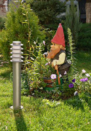 garden gnome on green grassy lawns among flowers photo