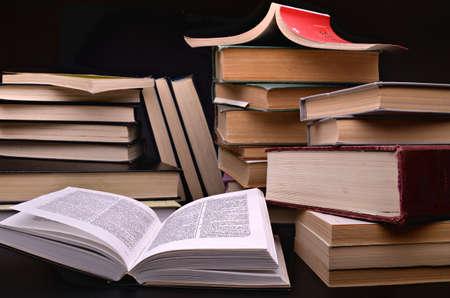 pile of books: libro aperto e la pila di libri su uno sfondo scuro