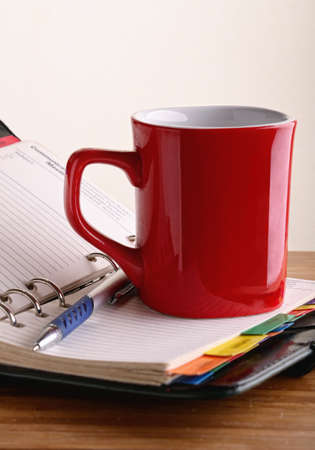 coffee breaks: red mug of coffee in the open notepad next to the pen Stock Photo