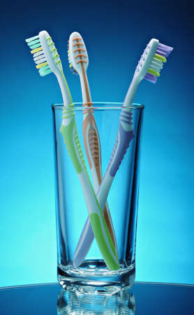 group of toothbrushes in a glass on a dark gradient background
