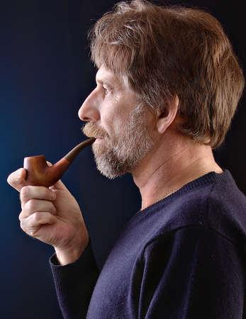 An elderly man with a pipe in his hand on a dark background Standard-Bild