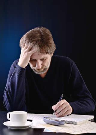 portrait of an elderly man at a desk on a dark background Standard-Bild
