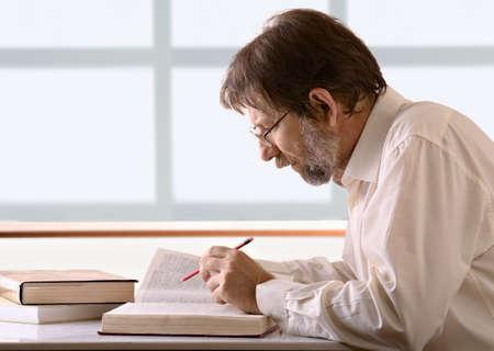 LTerer Mann mit einem Bleistift in der Hand an Ihrem Schreibtisch sitzen Standard-Bild - 12829444
