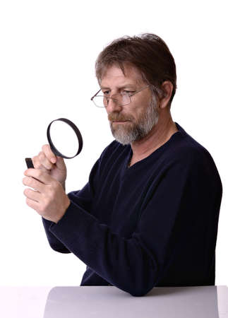 man with the magnifying glass in hand, considers the small object is isolated on a white background photo