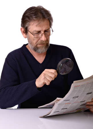 Thoughtful elderly man reading a newspaper with a magnifying glass in hand isolated on white background