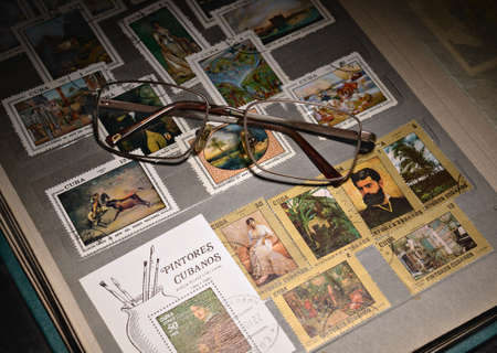 open album with colorful stamps and glasses, a collection of philatelist