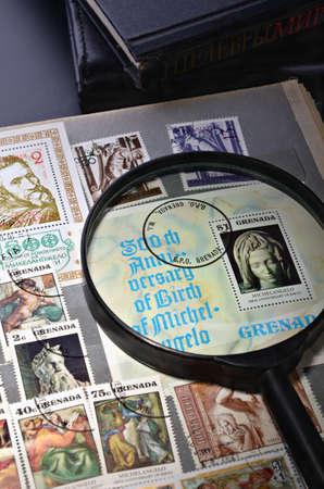 philatelist: Lupe auf einer Briefmarke im Album Philatelisten Lizenzfreie Bilder