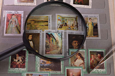 stamp collecting: magnifying glass on a postage stamp in the album philatelist