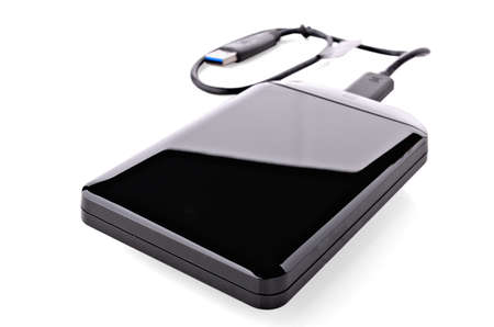 Versatile Hard Drive with USB cable on white background photo
