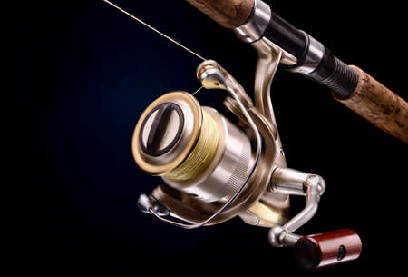 fishing equipment spinnig with coil on a dark background photo