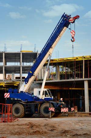 camion grua: maquinaria de construcción, grúa en una obra de construcción Editorial