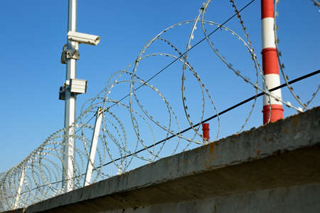 Security cameras and razor wire against a blue sky  photo
