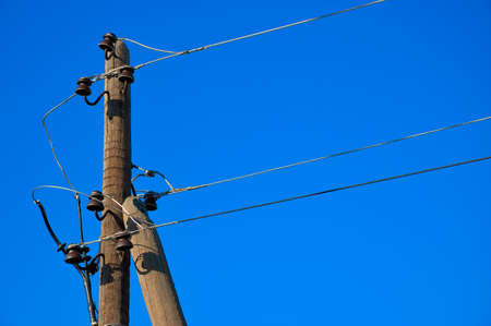 telegraphs: old wooden electric pole against a blue cloudless sky Stock Photo