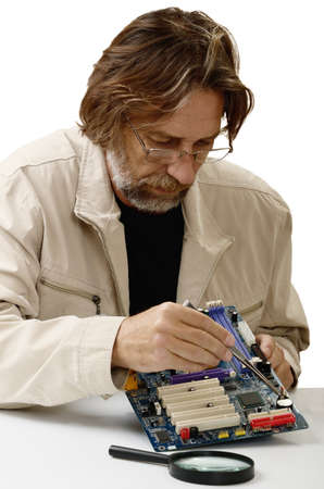techie: elderly man reconditioning computer on a white background