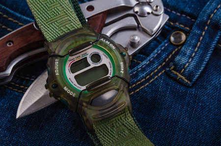 folding pocket knife and electronic watches over jeans photo