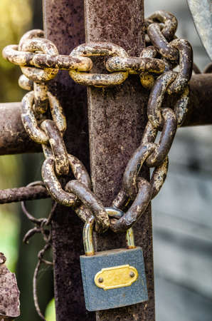 padlocks: old padlock with chain on metal gate Stock Photo