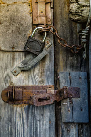 old padlock with chain on wooden gate photo