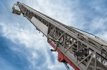 extends: A hydraulic man lift extends up to  blue sky Stock Photo