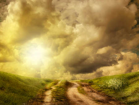 in thought: dirt road to the hill in the clouds (illustration of a fictional situation, in the form collage of photos)